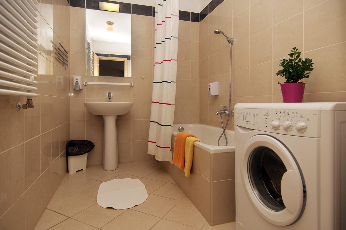 Стиральная машина в ванной комнате бежевой