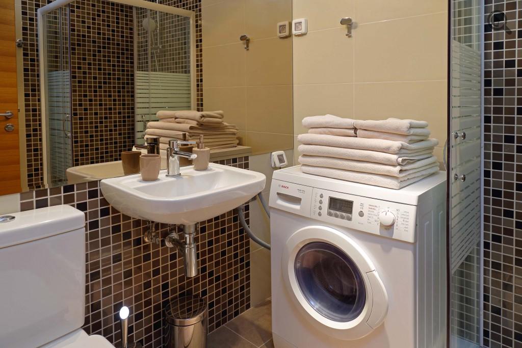 Стиральная машина в ванной комнате рядом с раковиной