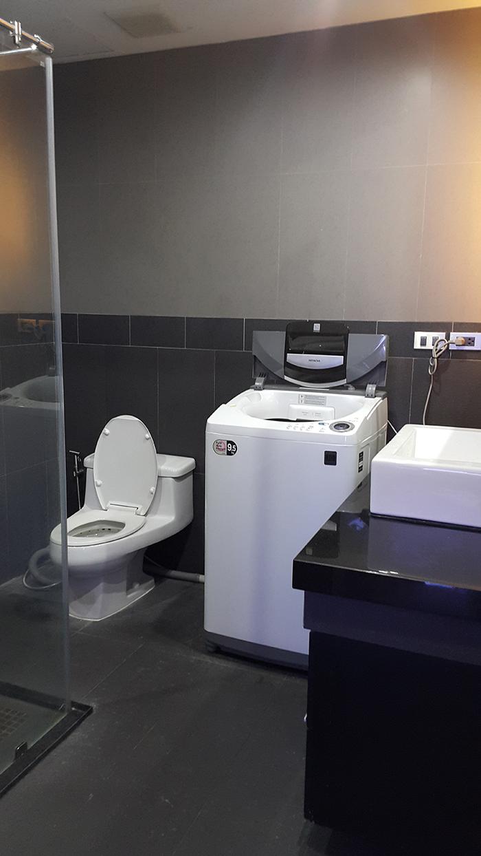 Стиральная машина в ванной комнате серой
