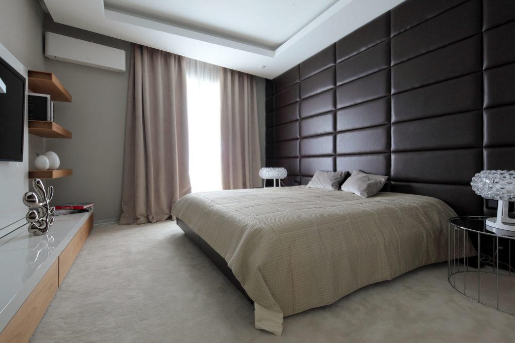 Черная мягкая панель со светлыми обоями в спальне