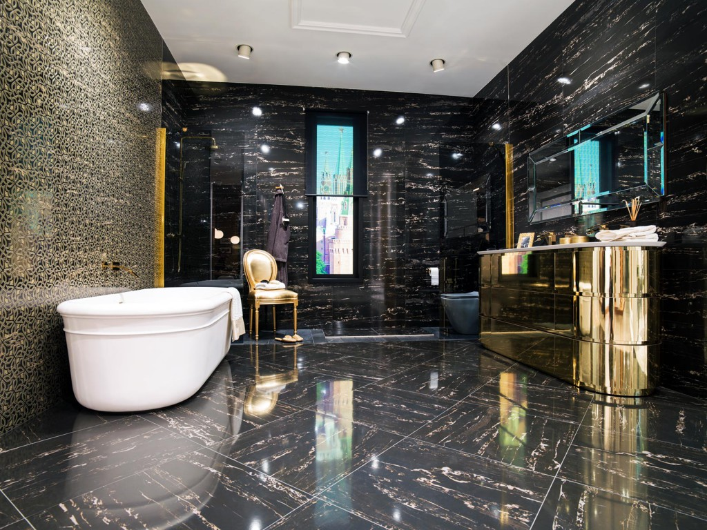Черная плитка с узорами с золотой мебелью в ванной