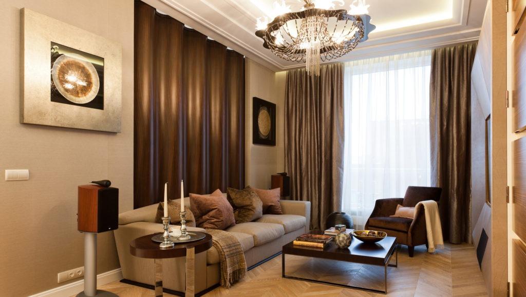 Коричнево-бежевый дизайн гостиной с подвесной объемной люстрой