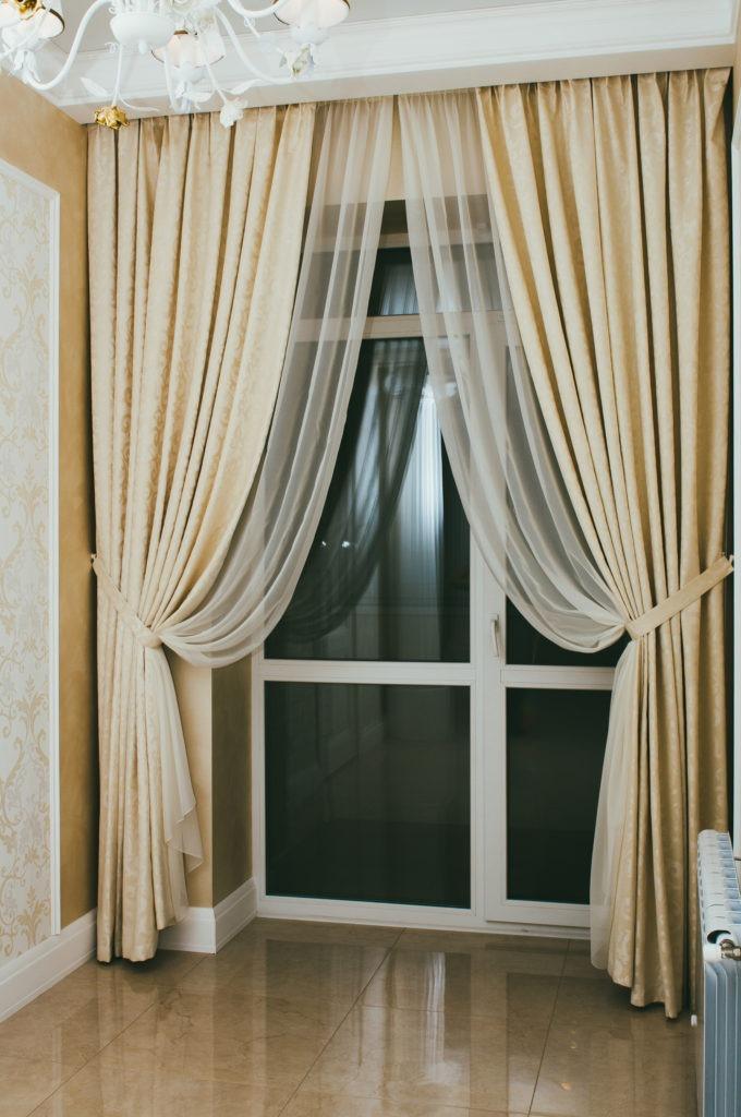 Изящные бежевые шторы для гостиной с балконом