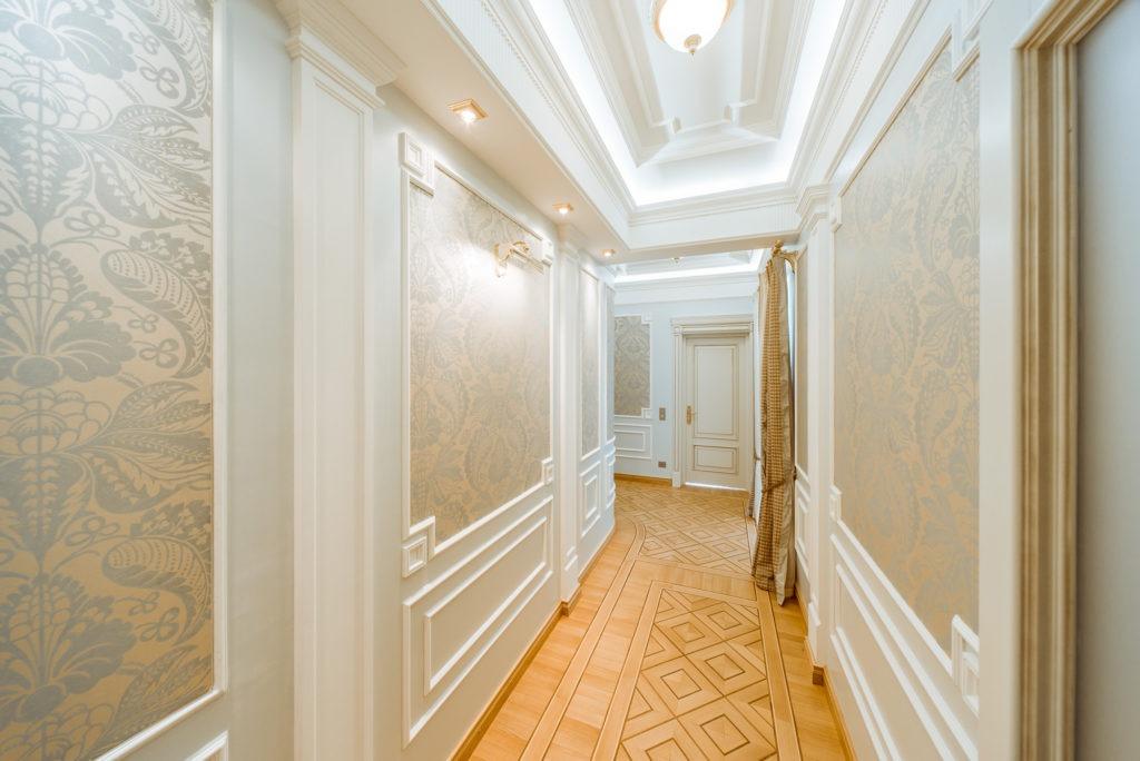 Деревянный пол с геометрическим рисунком и светлые двери в классическом интерьере