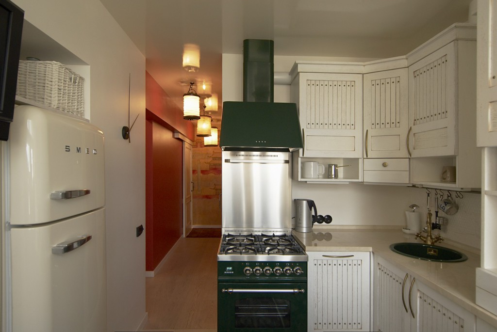 Белый холодильник в углу кухни