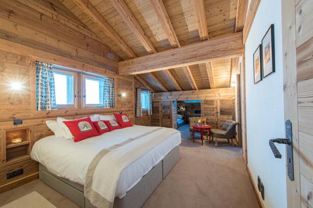 Просторная спальня с красными подушками под крышей в стиле кантри