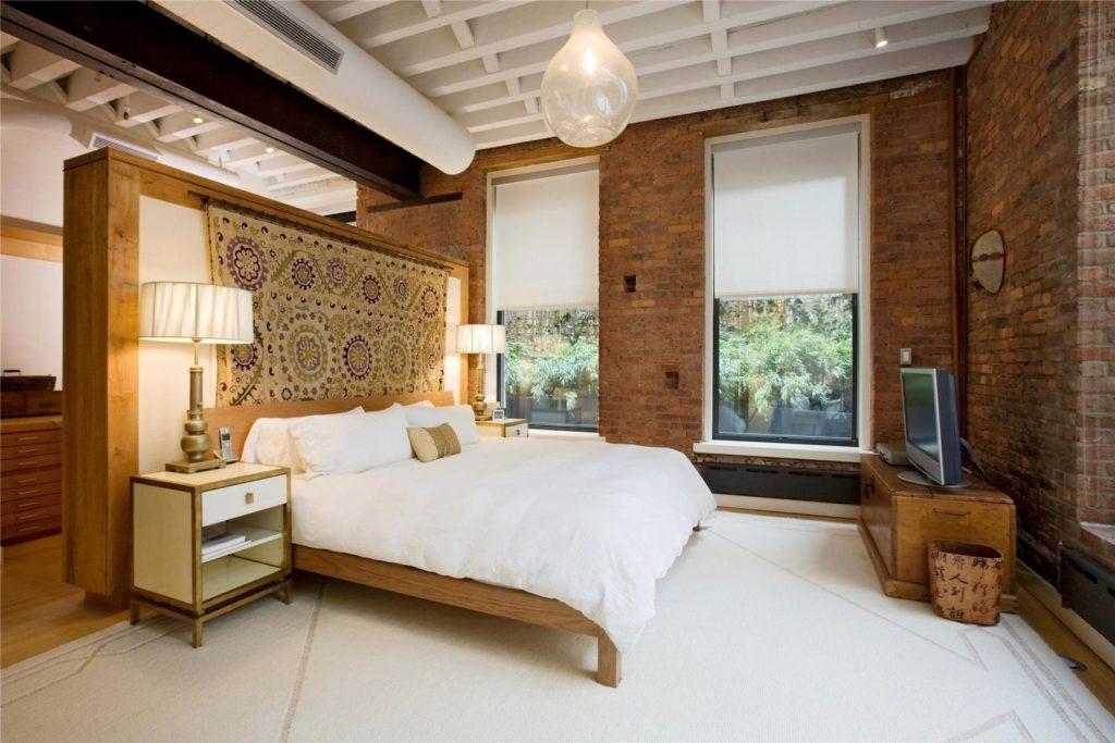 Красный кирпич придает спальне уют и динамику