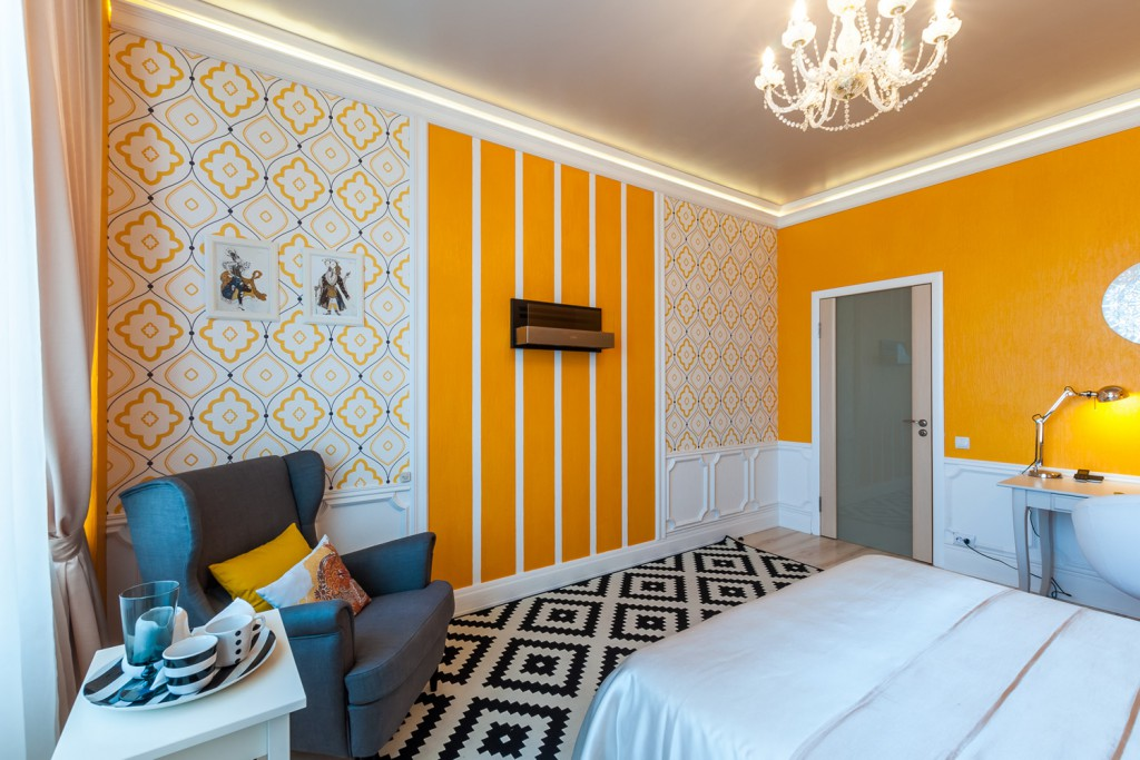 Яркое сочетание разных обоев с оранжевыми элементами в спальне