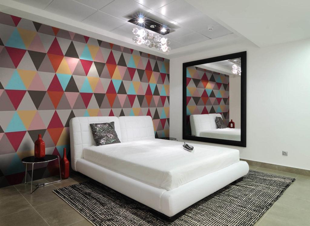 Яркие обои с геометрическим принтом в белой спальне