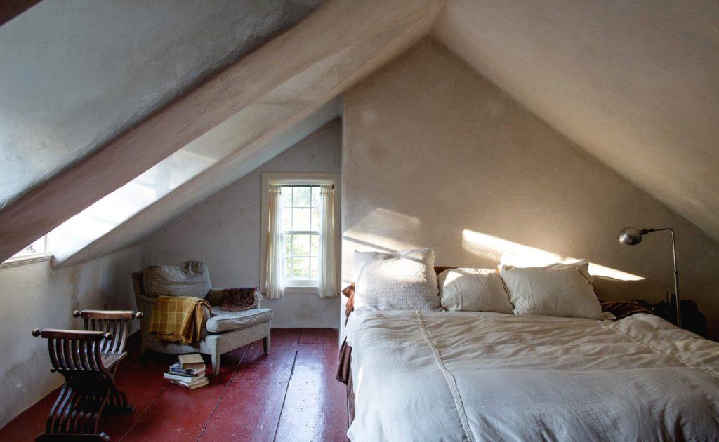 Простая спальня с красным полом в мансарде в стиле модерн