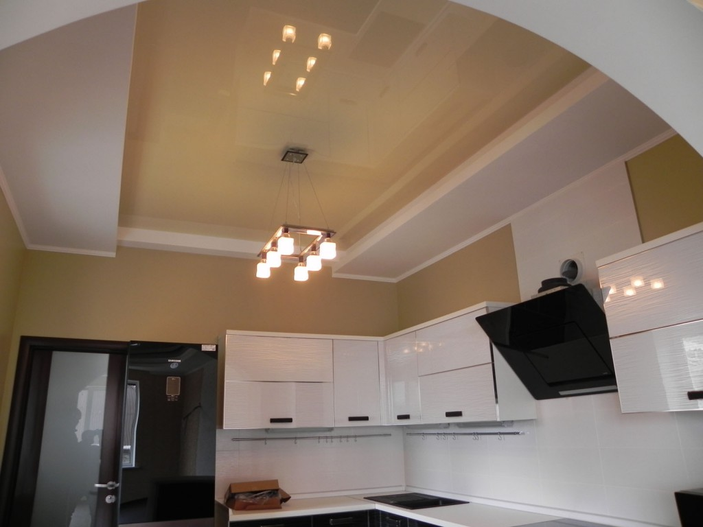 Люстра под глянцевым кремово-белым натяжным потолком на кухне