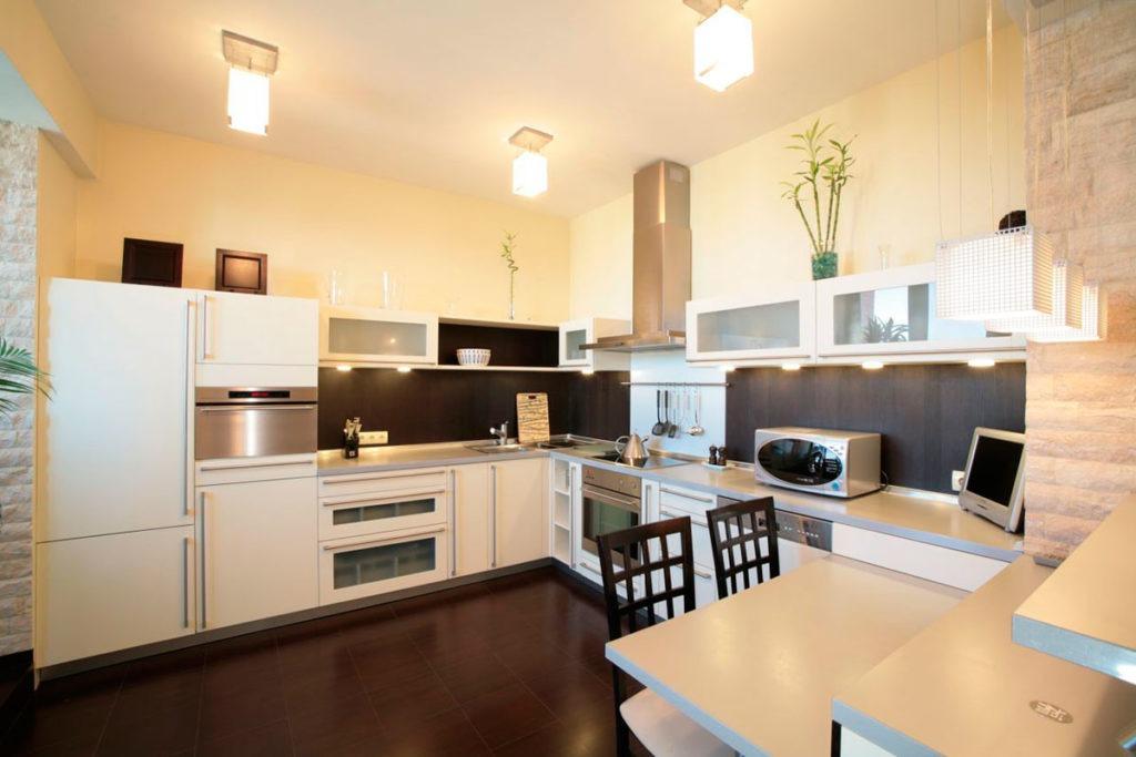 Белый натяжной потолок с ярким освещением на кухне