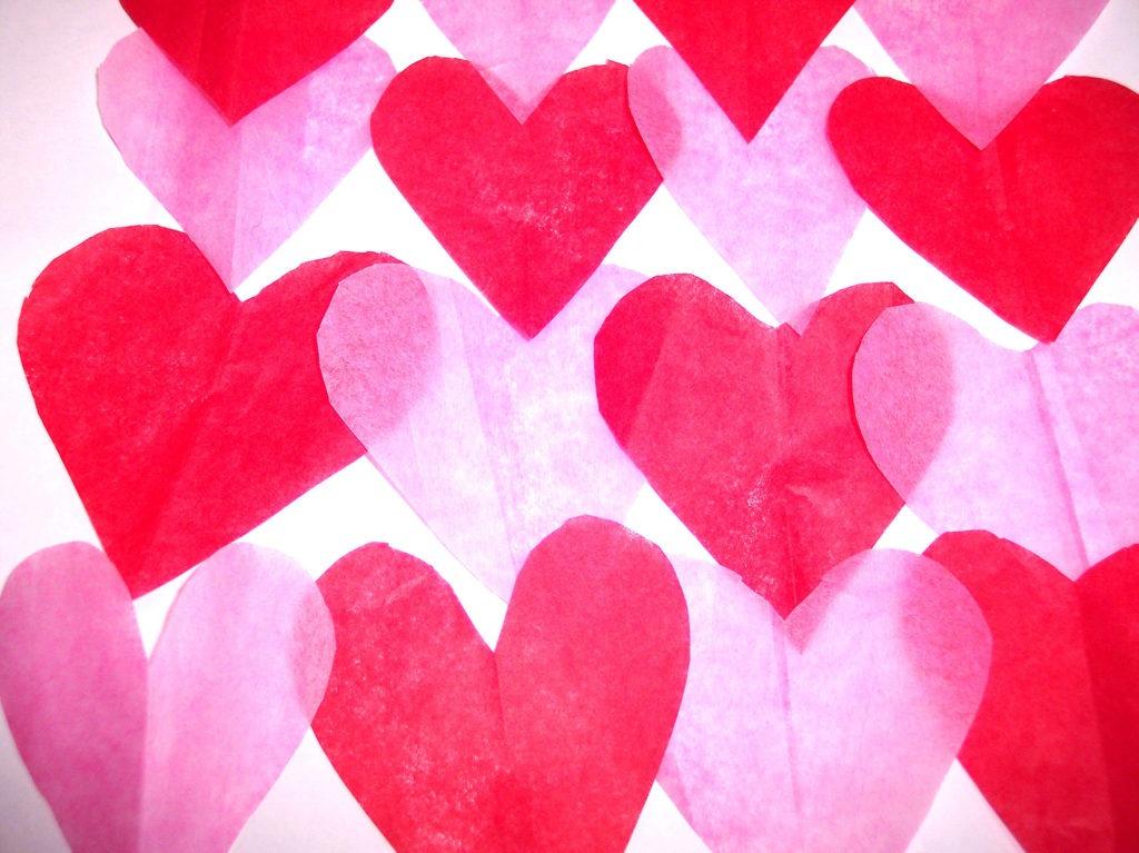Можно вырезать яркие сердечки из бумаги и разложить их на столе