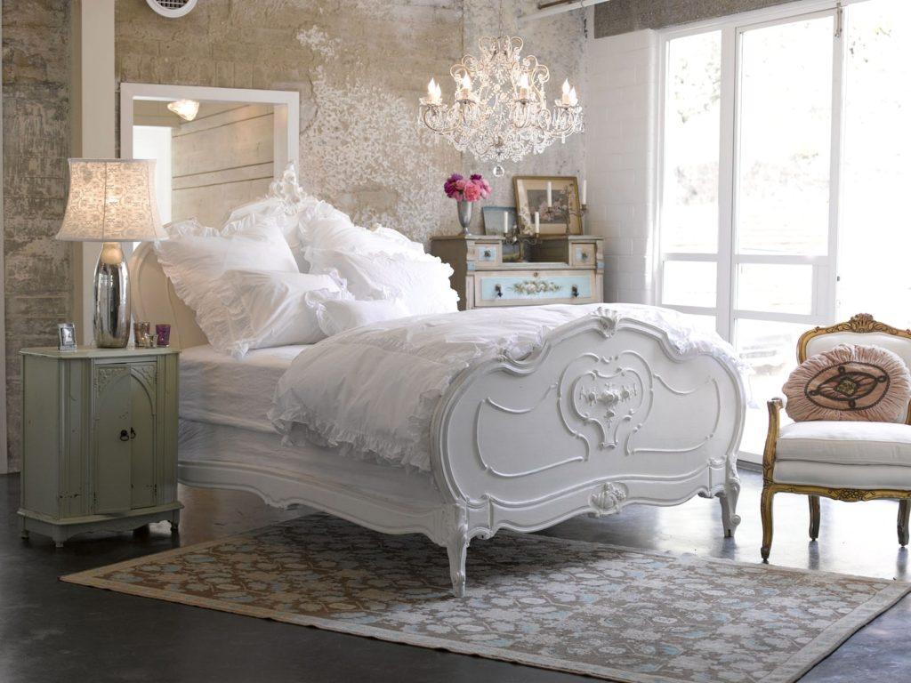 Спальня с необычной люстрой и белой кроватью в мансарде в стиле шебби шик