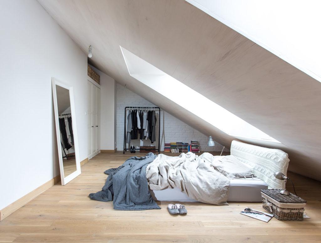 Минималистичная спальня в мансарде с кирпичной стеной