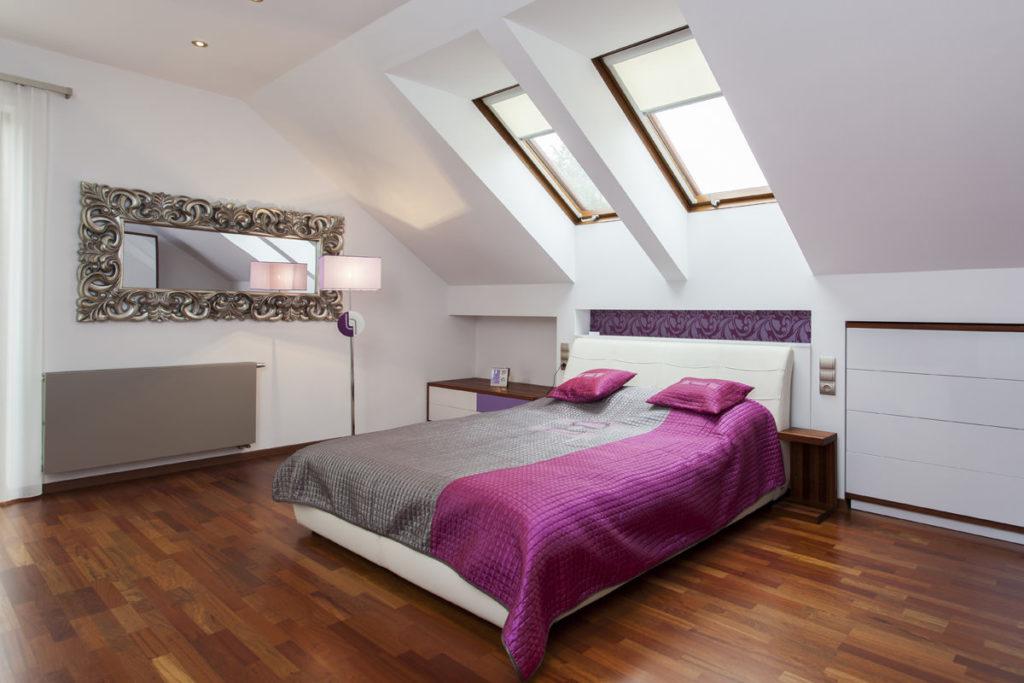 Мансардная спальня с розовыми элементами и коричневым полом