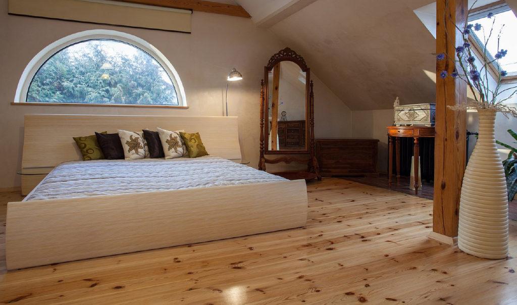 Мансардная спальня со светлым деревянным полом и полукруглым окном