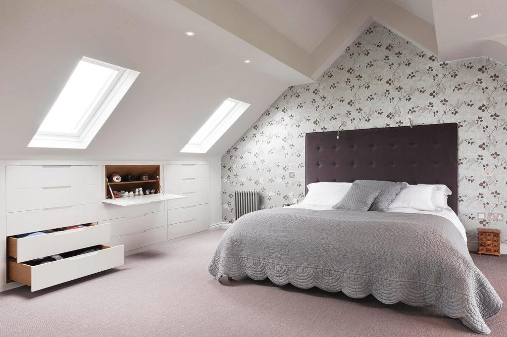 Мансардная спальня с цветочными обоями и встроенными ящиками для хранения