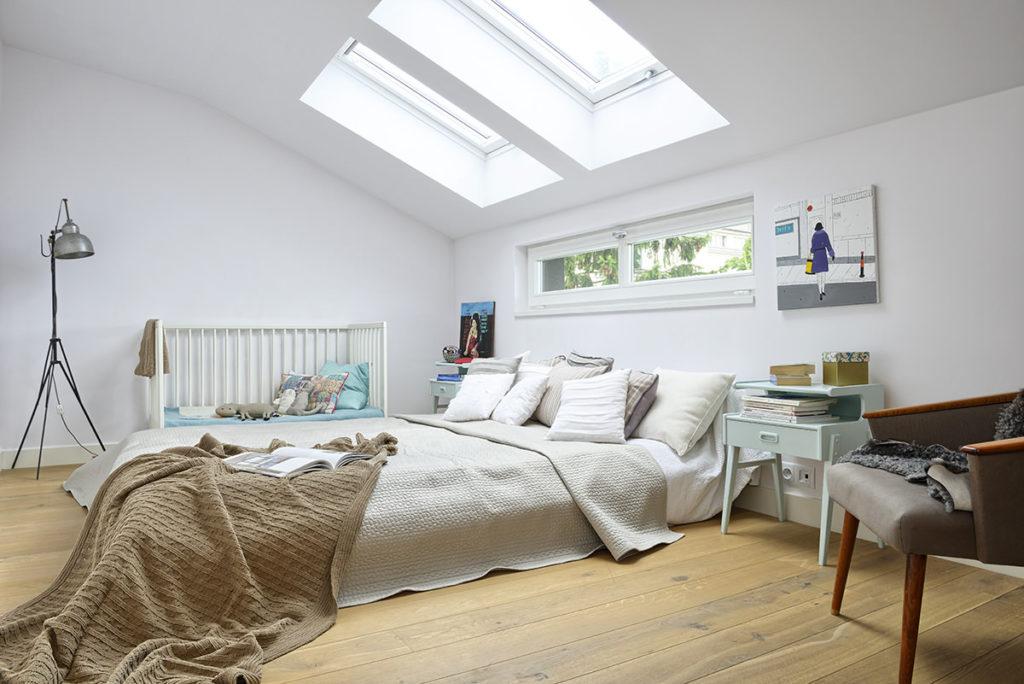 Светлая мансардная спальня с детской кроваткой