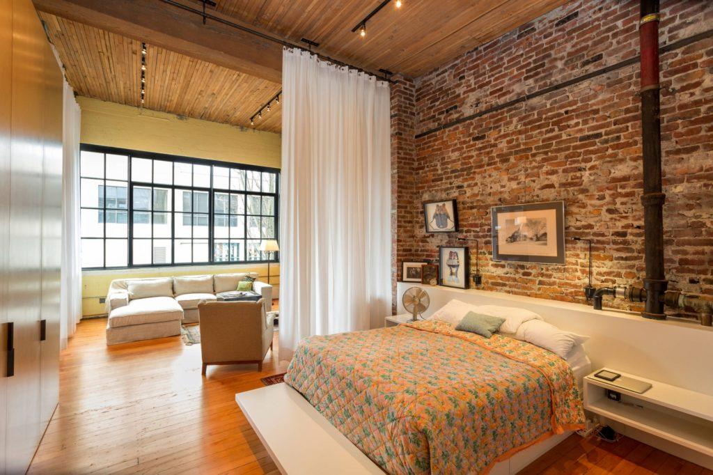 Спальня с кирпичными стенами в стиле лофт