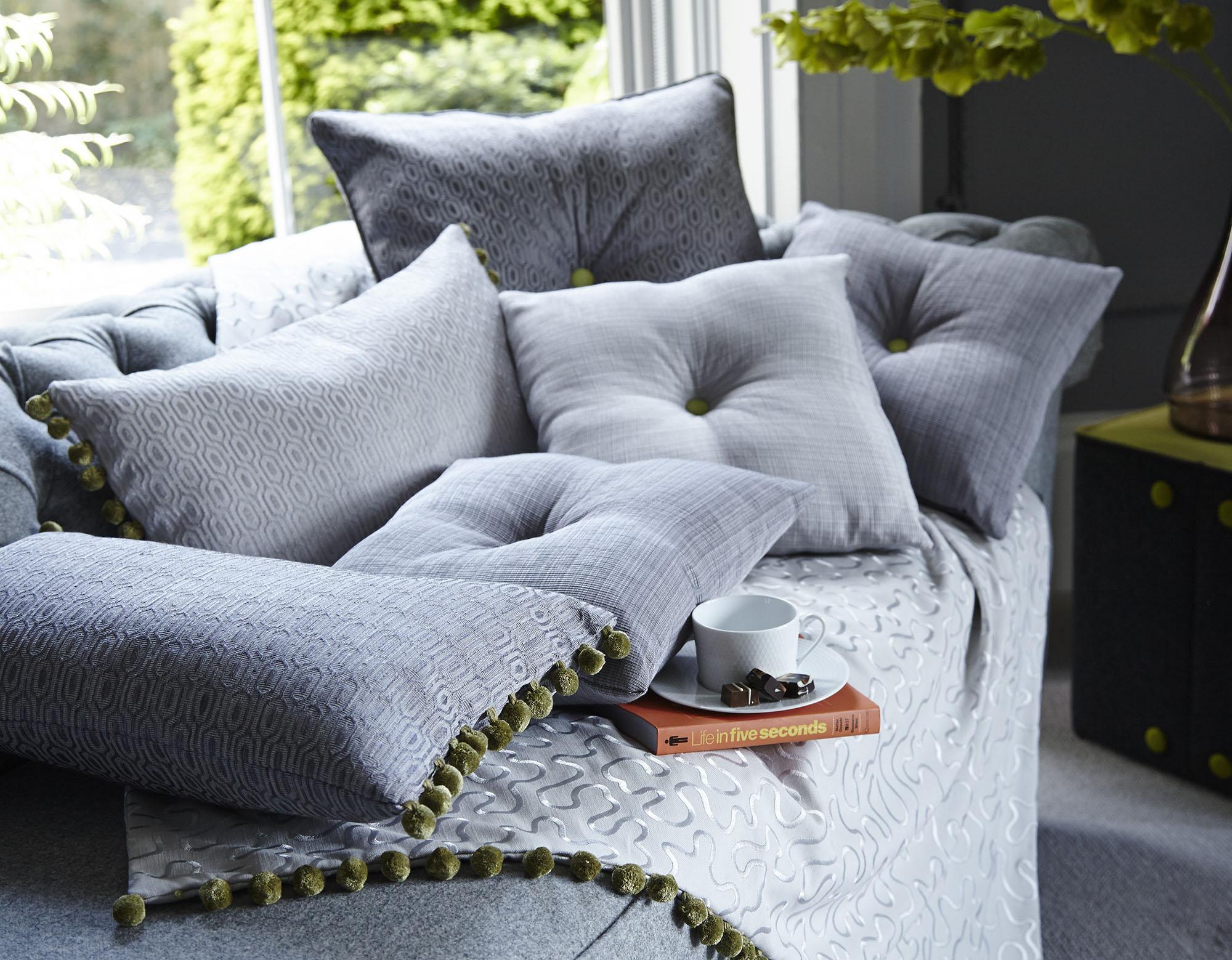 Красивые серые декоративные подушки с зелеными акцентами