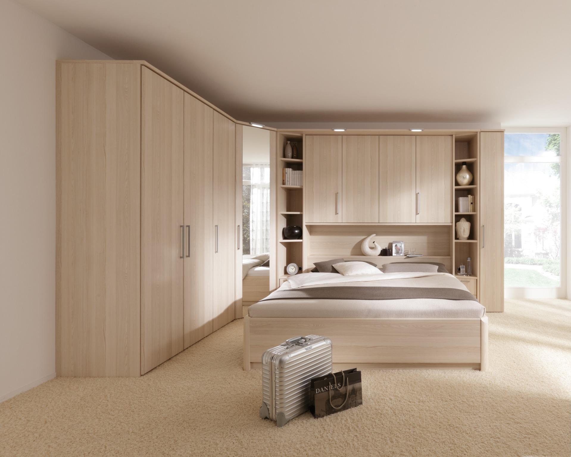 Угловой шкаф в интерьере спальни деревянный