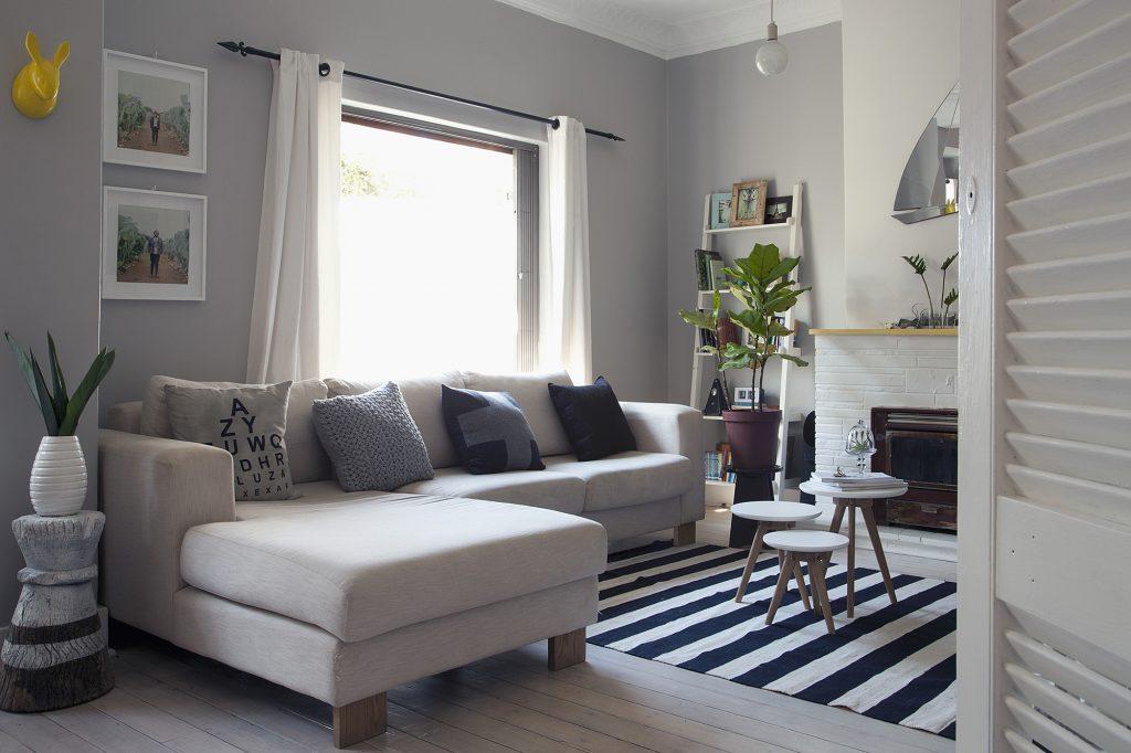 Стильный светло-серый диван в гостиной в скандинавском стиле