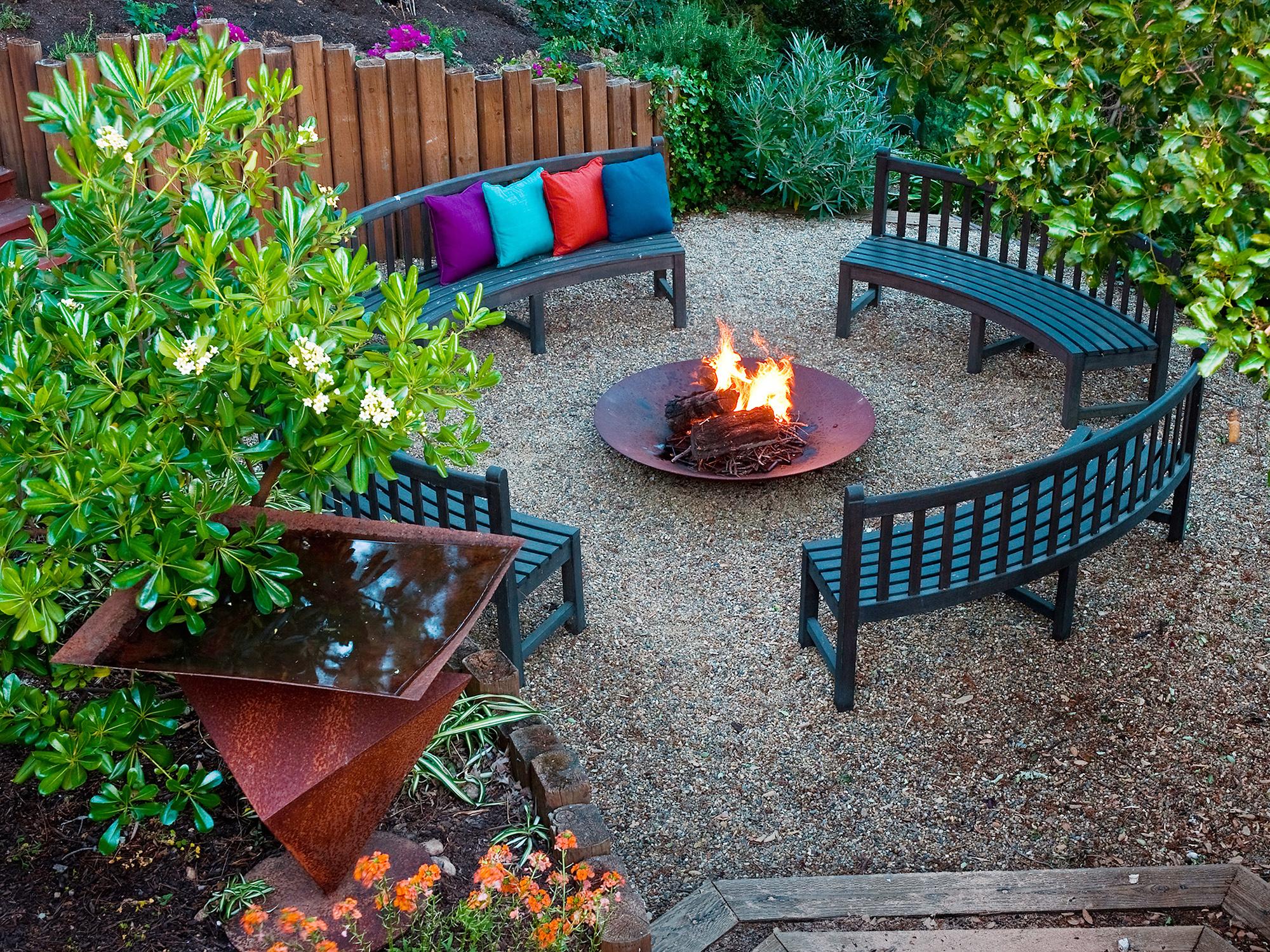 Полукруглые скамейки, декоративные растения и заборчики во дворе