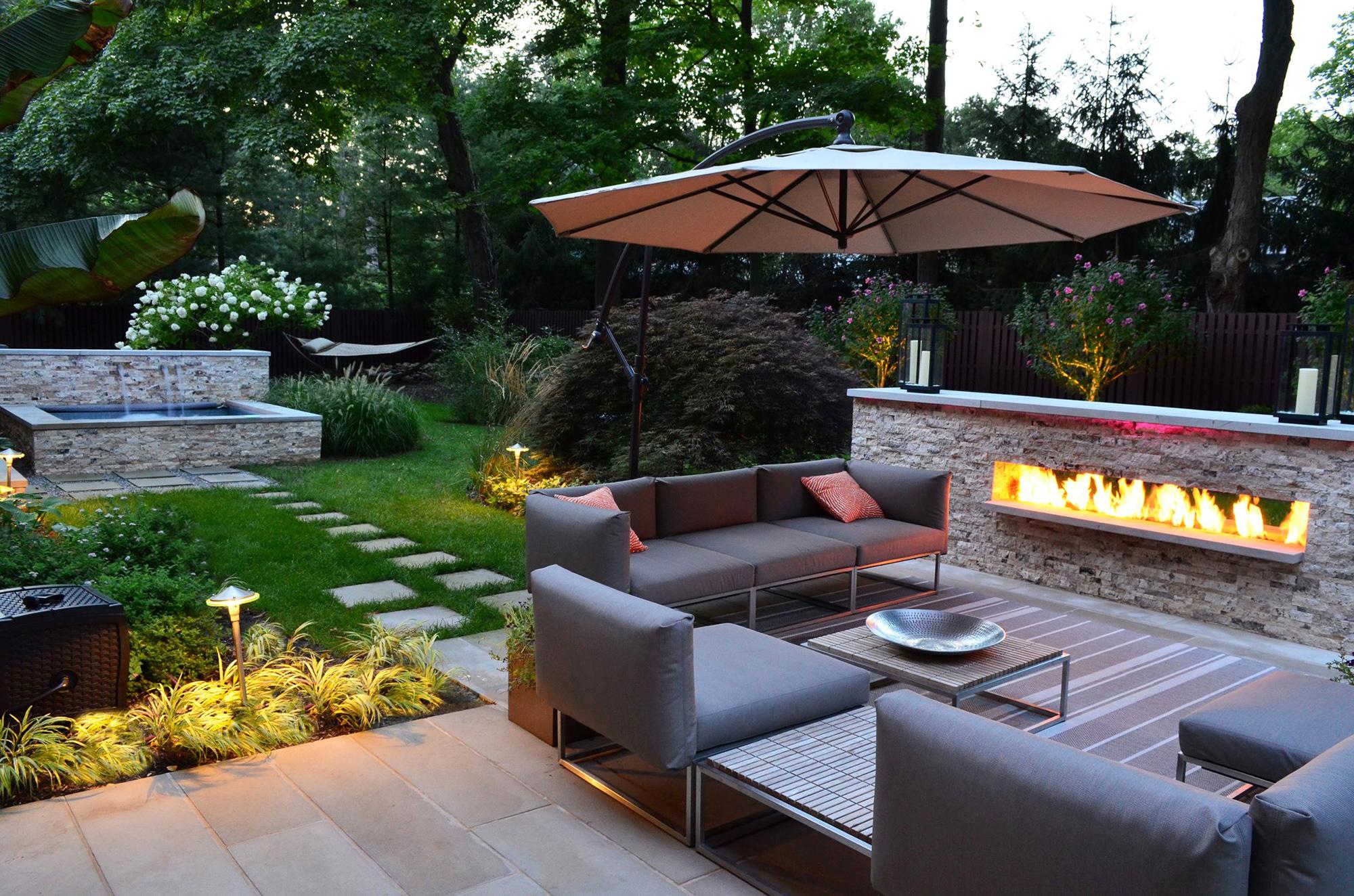 Мебель, камин и фонтан в дизайне двора загородного дома