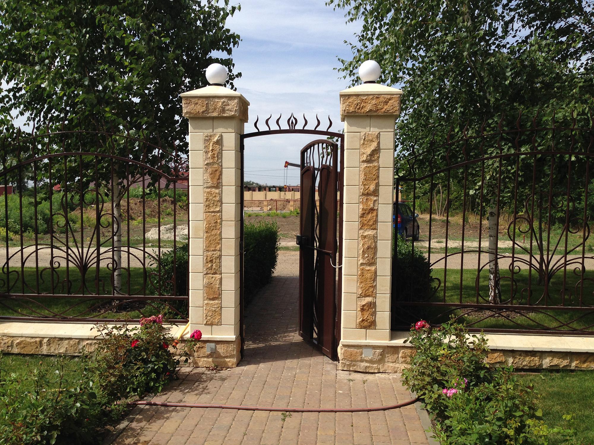 Забор из камня и металлических кованых элементов