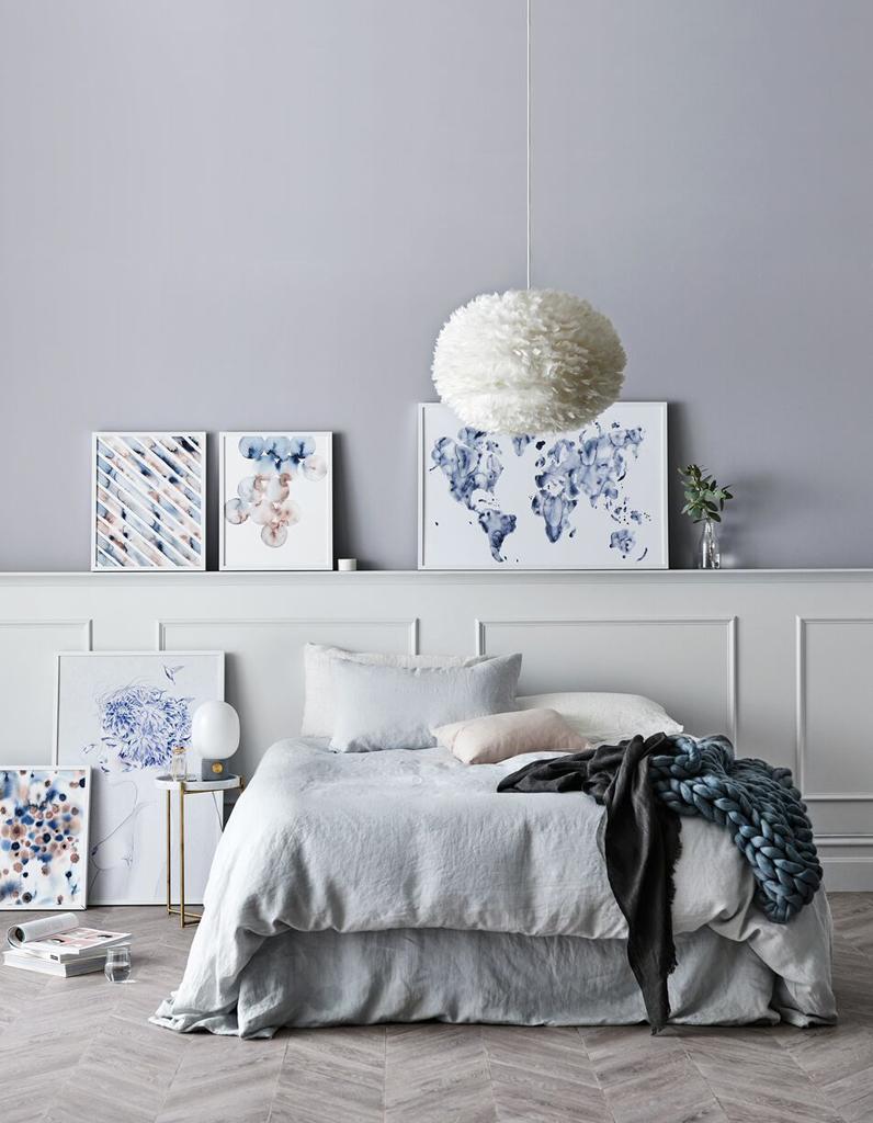 Картина в голубых цветах над кроватью в спальне