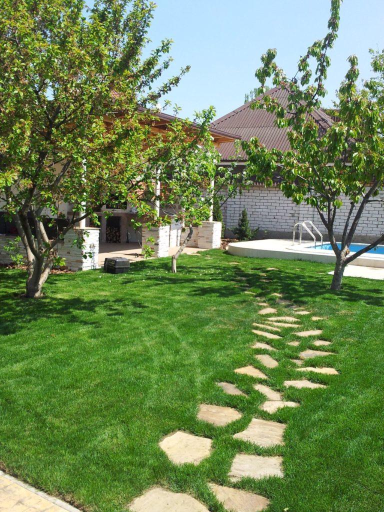 Каменная садовая дорожка, уложенная на траву