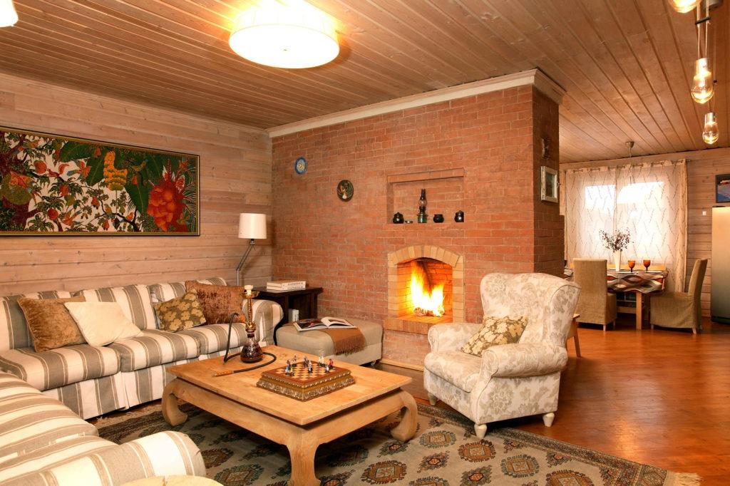 Гостиная с камином в кирпичной стене в деревенском стиле