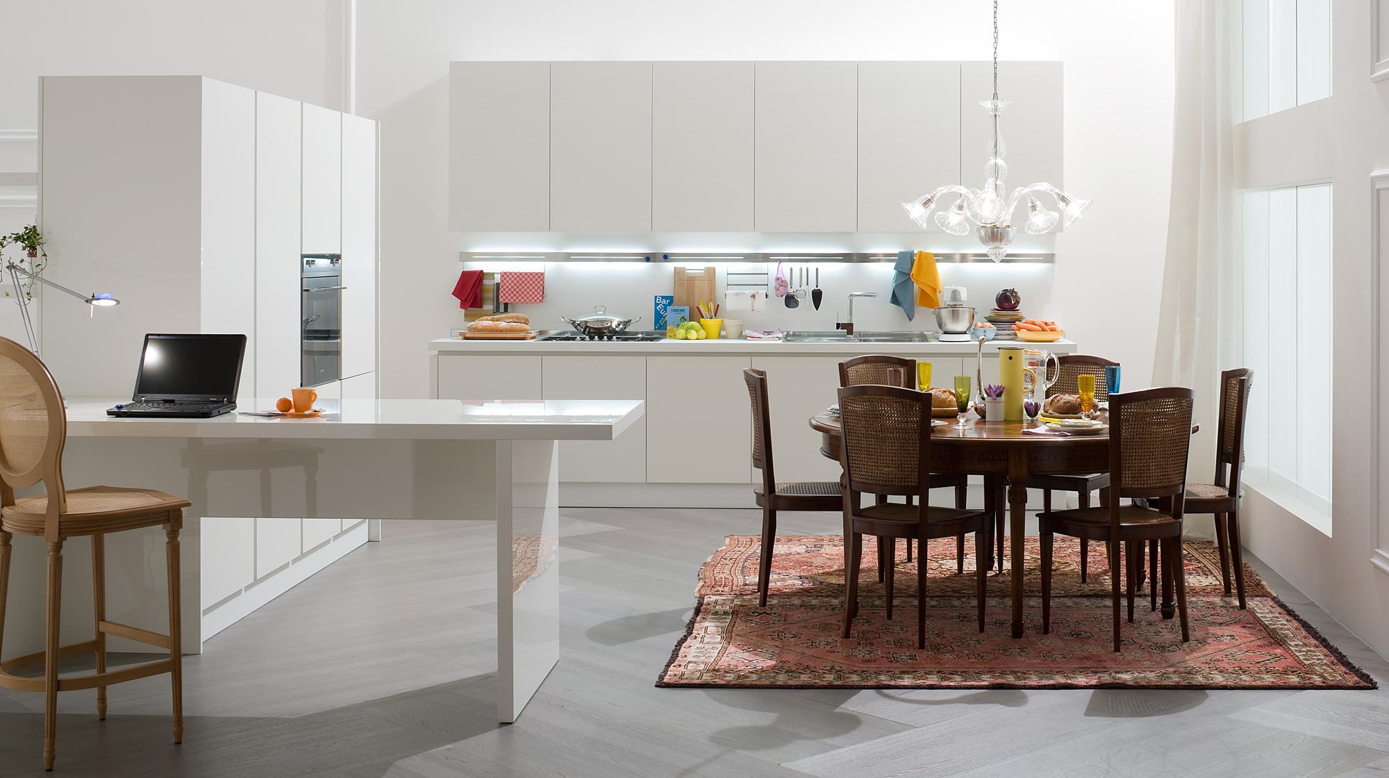 Сочетание белой кухни в стиле хай-тек и уютной обеденной зоны с коврами