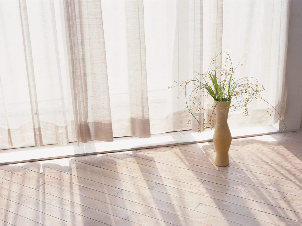Небольшая бежевая напольная ваза с живыми растениями