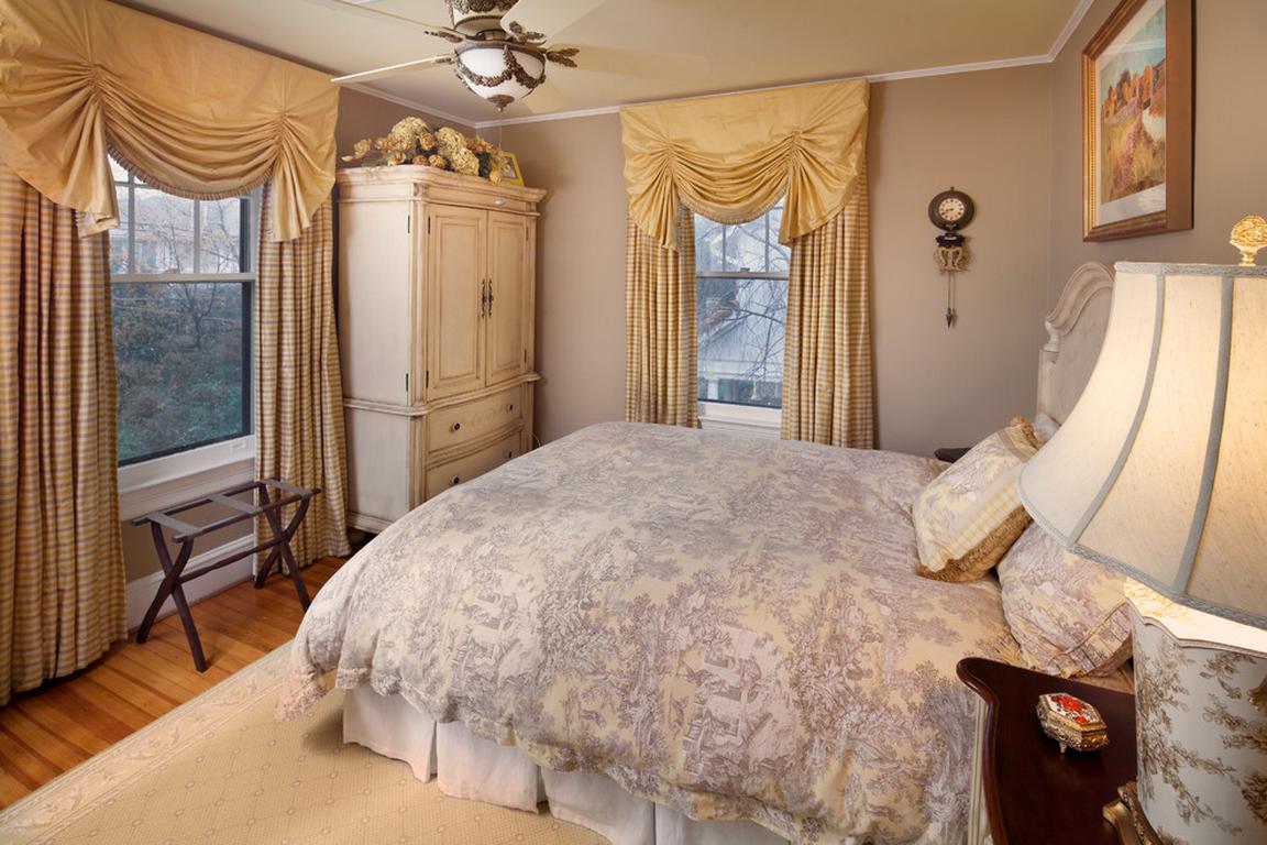 Бежевые шторы с ламбрекенами в спальне