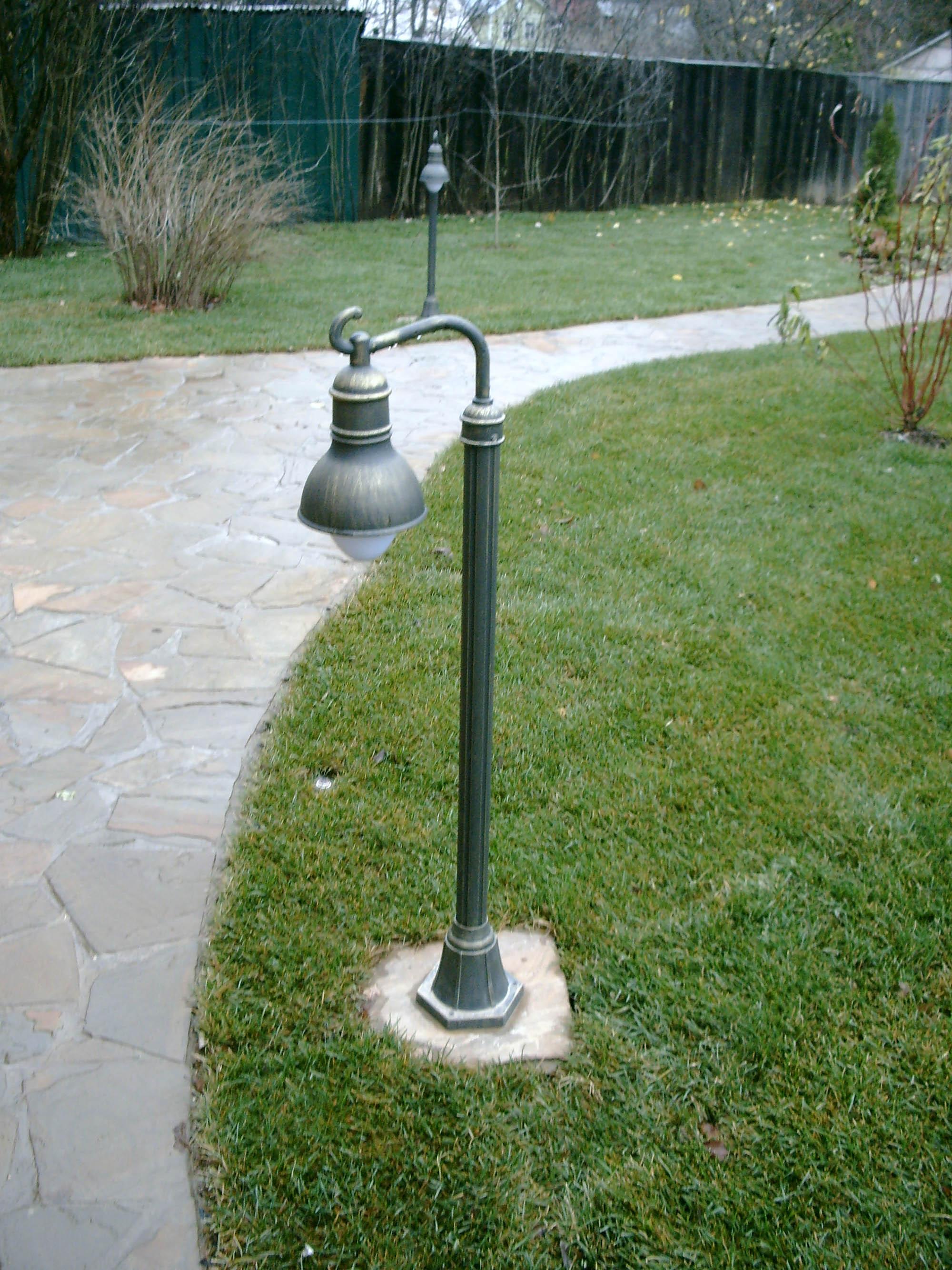 Декоративный невысокий фонарь в саду