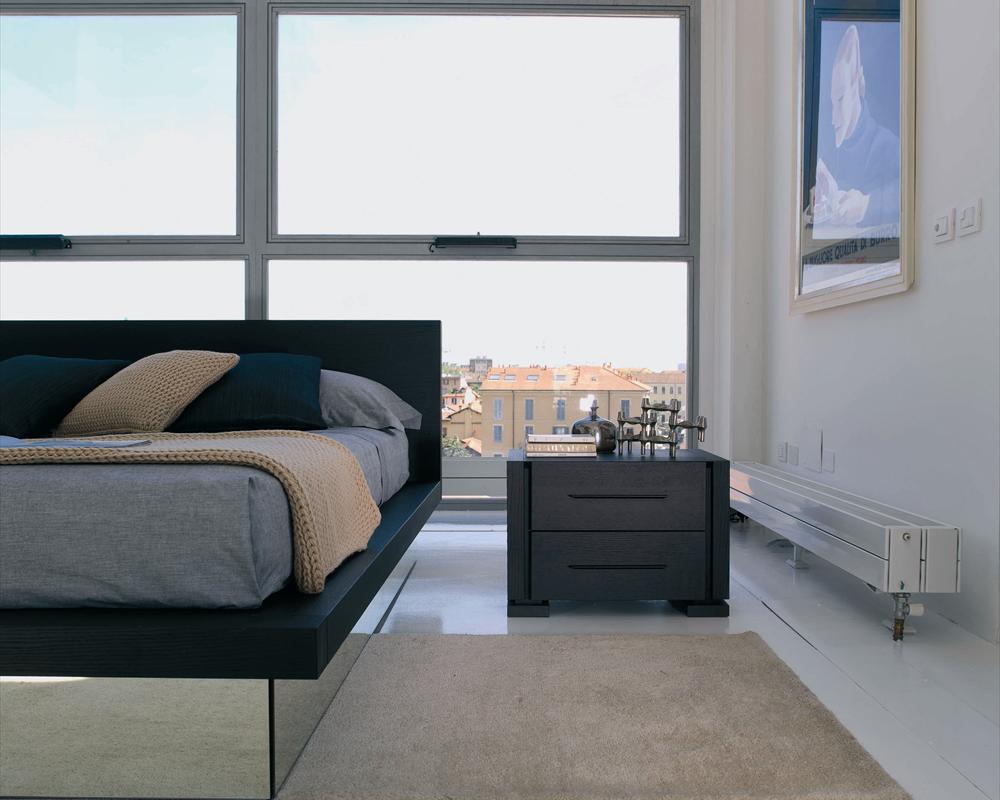 Черная прикроватная тумба из дерева в современной спальне