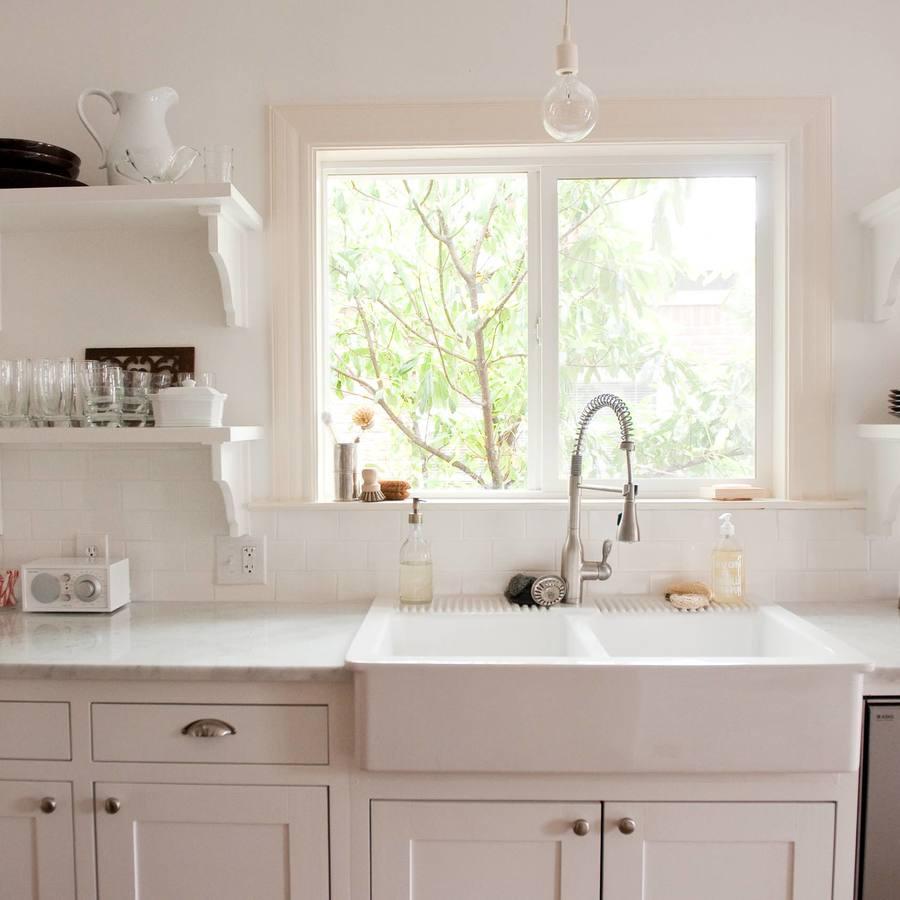Белая двойная мойка у окна на кухне
