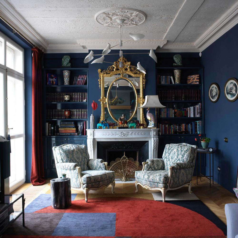 Синие стены и красные шторы и акцент на ковре в гостиной