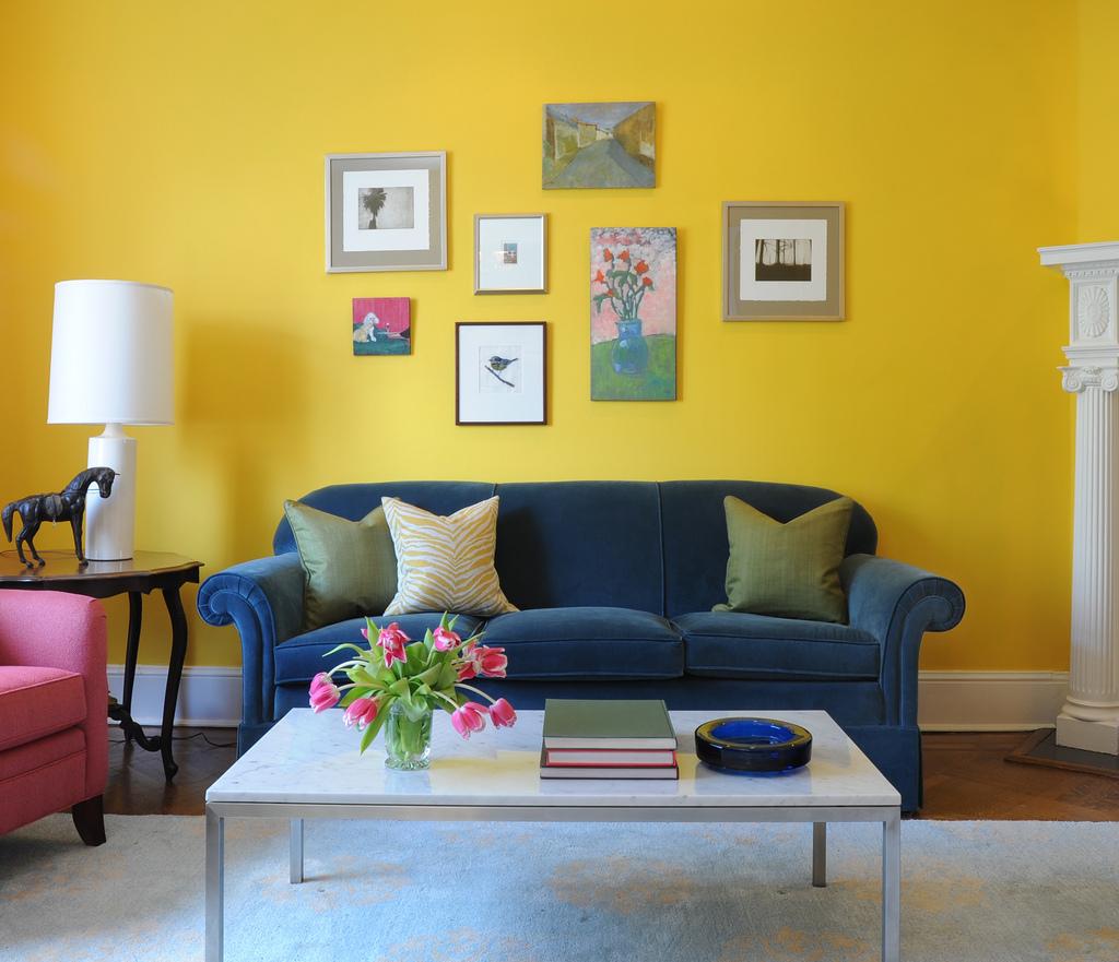 Синий диван и желтая стена в гостиной