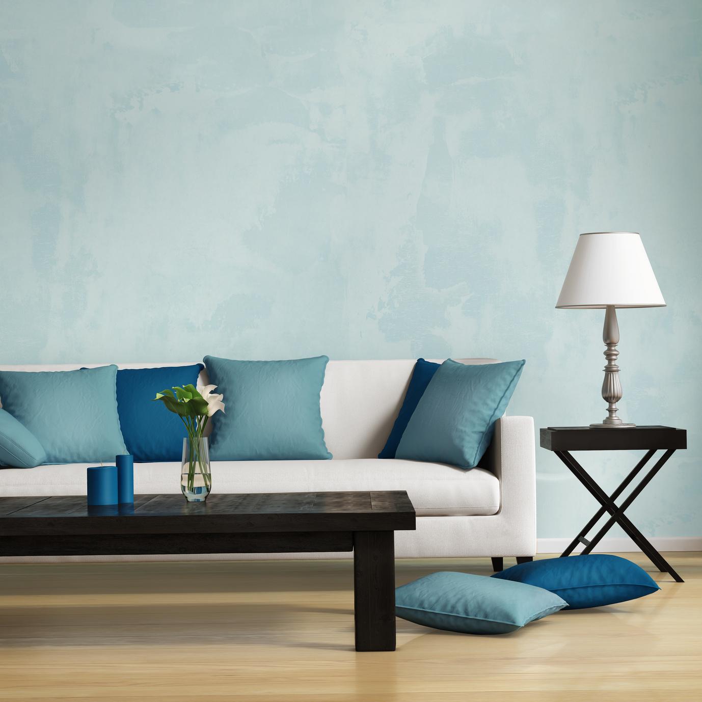 Бежевый пол и синие подушки в гостиной