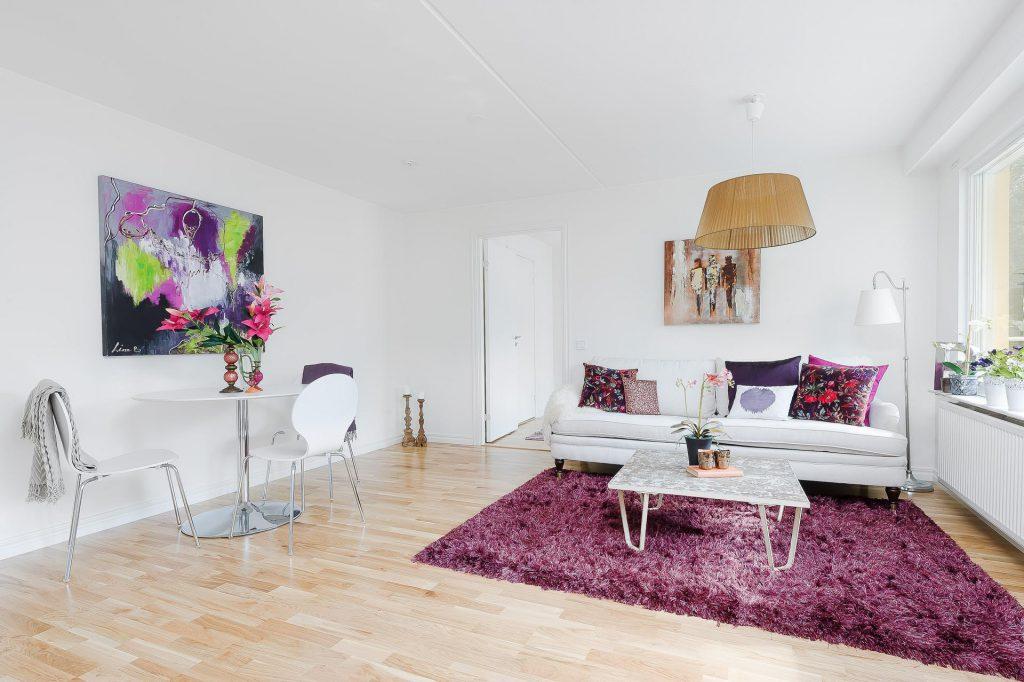 Сиреневый ковер и другие элементы в светлом интерьере гостиной