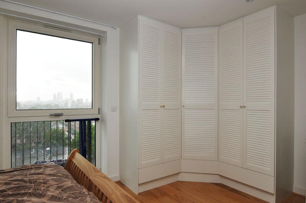 Белый распашной угловой шкаф в спальне