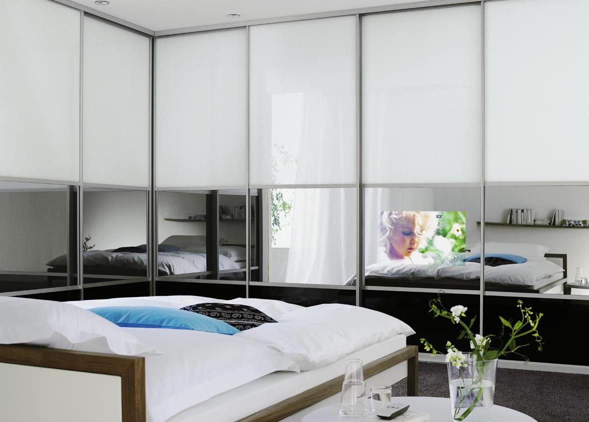 Большой угловой шкаф-купе со встроенным телевизором в спальне