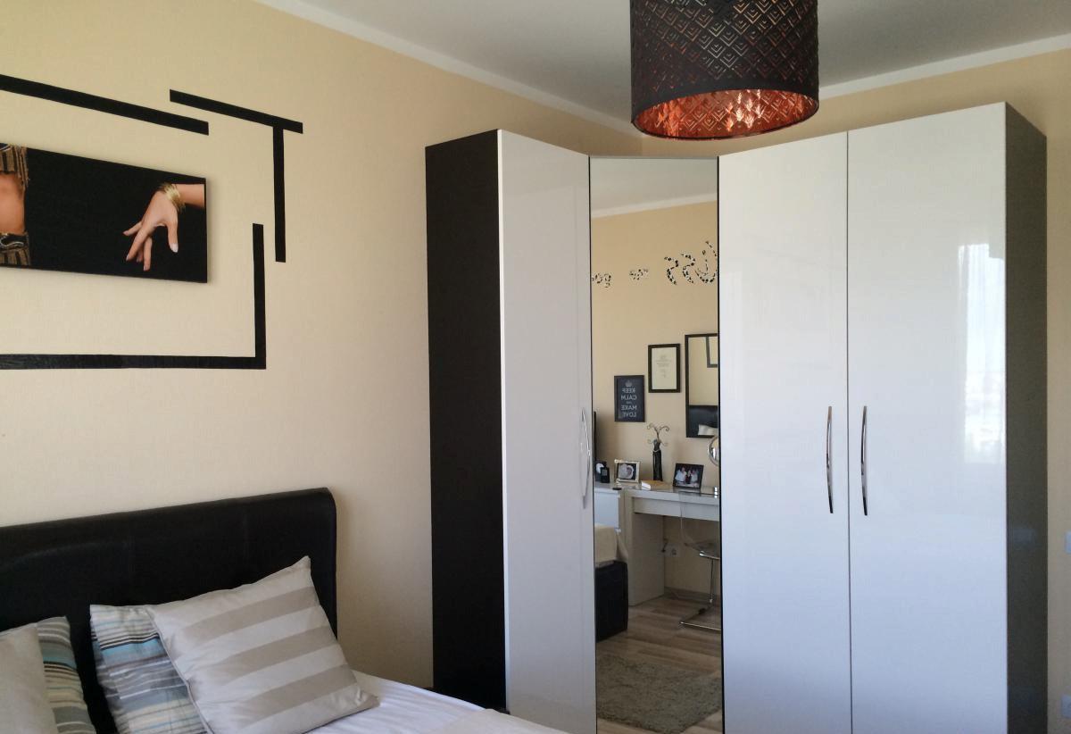 Черно-белый угловой шкаф с зеркалом в спальне