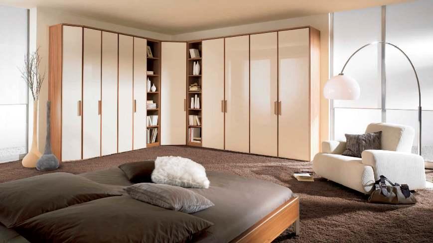 Коричнево-бежевый угловой шкаф в просторной спальне