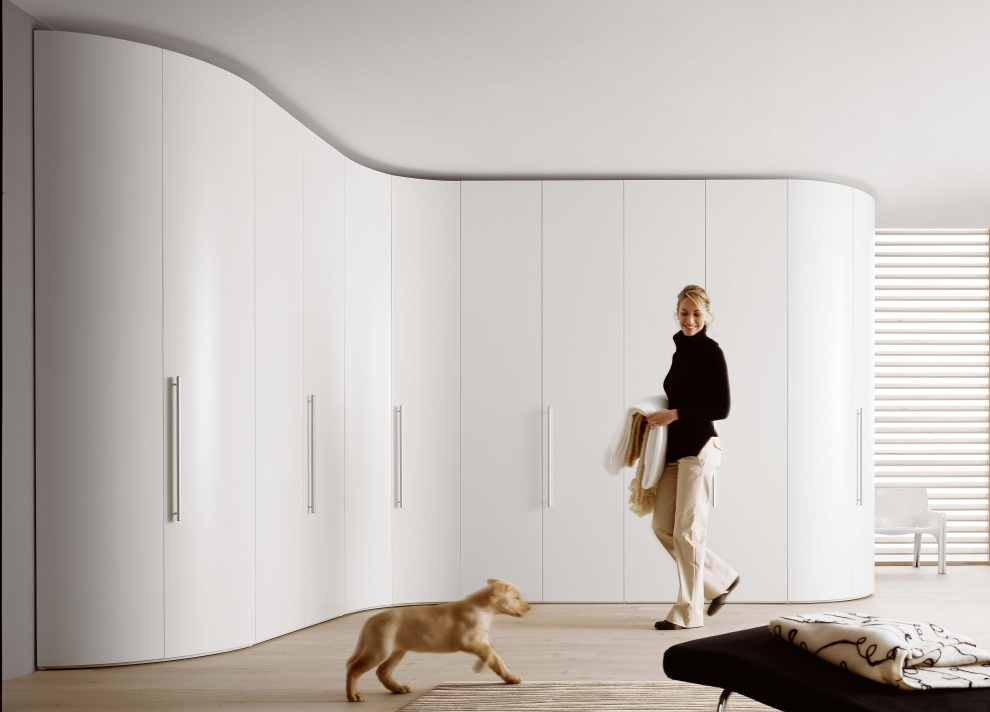 Белый радиусный угловой шкаф в спальне