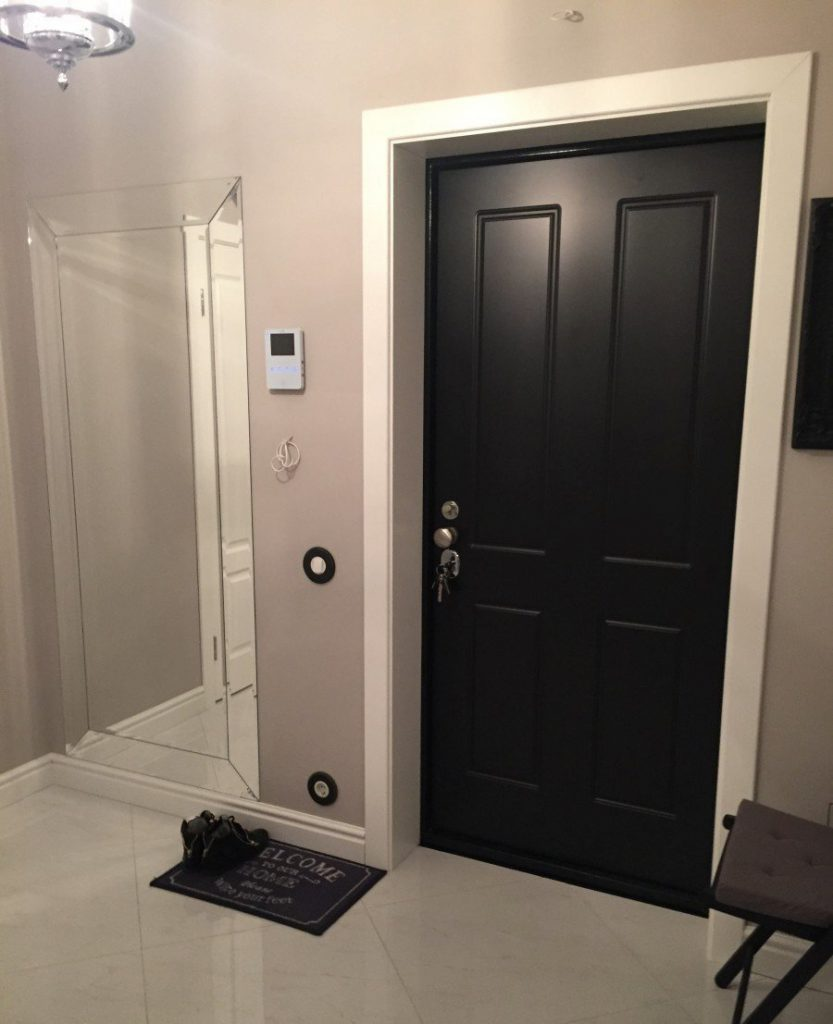 Черная входная дверь в прихожую с серыми обоями