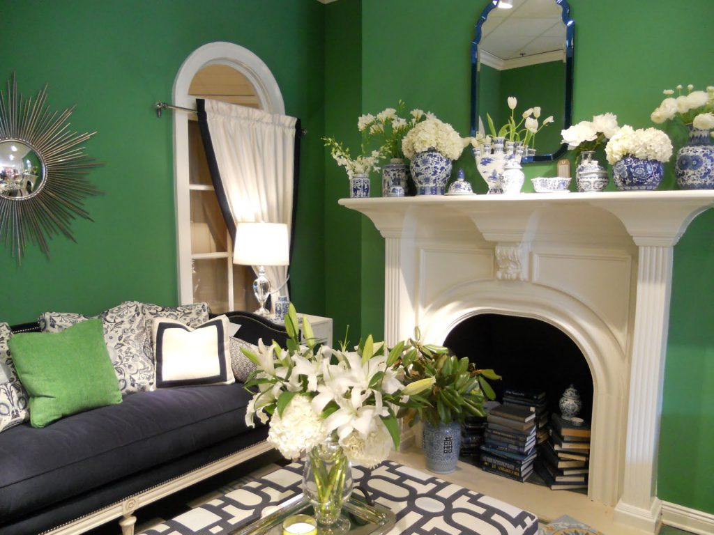 Гостиная с зелеными стенами и белым стилизованным камином